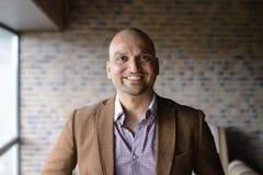 Portrait d'homme indien bel heureux d'affaires, souriant, sûr et amical à l'intérieur Image libre de droits