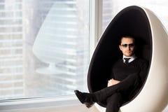 Portrait d'homme mystérieux élégant dans la chaise futuriste d'oeufs Image libre de droits