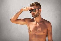 Portrait d'homme nu non rasé bel dans des lunettes de soleil, gardant sa main sur le front, examinant la distance posant contre l images stock