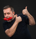 Homme plus âgé avec le poivron rouge dans sa bouche Photographie stock libre de droits