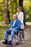 Portrait d'homme plus âgé sur le fauteuil roulant avec l'infirmière extérieure Photographie stock libre de droits