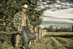 Portrait d'homme rustique dans le chapeau avec la chemise déboutonnée se penchant sur la barrière en bois photos libres de droits