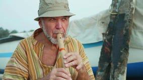 Portrait d'homme supérieur jouant la cannelure en bambou sur la plage à côté du bateau de pêche clips vidéos
