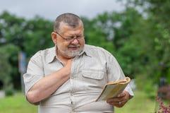 Portrait d'homme supérieur lisant un livre intéressant Images libres de droits
