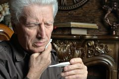 Portrait d'homme supérieur malade avec le thermomètre Photographie stock libre de droits