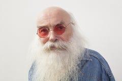 Portrait d'homme supérieur portant les lunettes rouges au-dessus du fond gris Photographie stock libre de droits