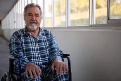 Portrait d'homme supérieur se reposant sur le fauteuil roulant dans la maison de repos Image stock