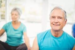 Portrait d'homme supérieur souriant avec l'épouse méditant Image stock