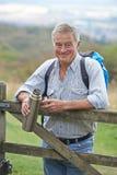 Portrait d'homme supérieur sur la hausse dans la campagne se reposant par la porte Image libre de droits