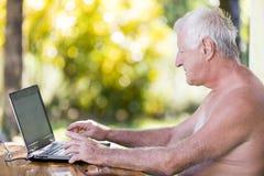 Portrait d'homme supérieur travaillant avec l'ordinateur portable dans extérieur sans chemise image libre de droits