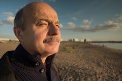 Portrait d'homme d'une cinquantaine d'années détendant sur la nature dans le jour d'été et regardant loin la distance Photographie stock libre de droits
