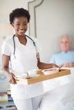 Portrait d'infirmière de sourire avec le petit déjeuner dans le plateau tandis qu'homme supérieur se trouvant sur le lit Photographie stock