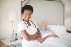 Portrait d'infirmière de sourire se tenant avec des bras croisés tandis qu'homme supérieur se trouvant sur le lit Photo stock
