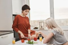 Portrait d'intérieur de la femme chaude attirante s'asseyant sur le tomotoe de coupe de table tandis que son amie boit du jus dan Photo stock