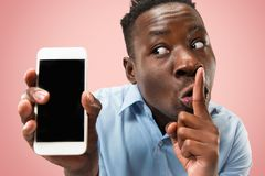 Portrait d'intérieur du jeune homme de couleur attirant tenant le smartphone vide photos libres de droits
