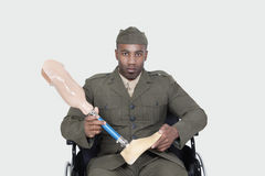 Portrait d'officier militaire des USA dans le fauteuil roulant tenant le pied de prothèse au-dessus du fond gris Photos stock