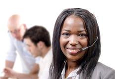 Portrait d'opérateur africain gai de sourire de téléphone de soutien dans h Photo libre de droits