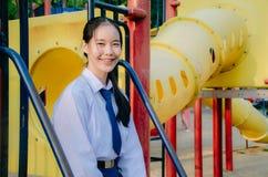 Portrait d'?tudiante asiatique dans le style de la Tha?lande d'uniforme scolaire, se reposant sur l'oscillation et s'amuser dans  photographie stock