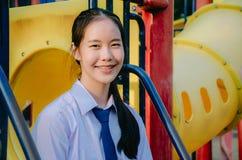 Portrait d'?tudiante asiatique dans le style de la Tha?lande d'uniforme scolaire, se reposant sur l'oscillation et s'amuser dans  images stock