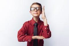 Portrait d'un écolier positif et émotif, tractions sa main au conseil, fond blanc, verres, chemise rouge, thème d'affaires, photographie stock libre de droits