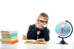 Portrait d'un écolier rêveur à une table avec des livres et un globe Image libre de droits