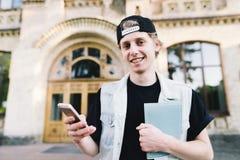 Portrait d'un étudiant de sourire employant un téléphone portable et des prises un carnet sur le fond du bâtiment d'université images libres de droits