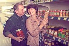 Portrait d'un achat plus âgé de couples casse-croûte au sto d'épicerie Image stock