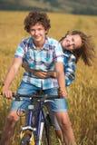 Portrait d'un ado sur une bicyclette voyageant dans le domaine de seigle Photo stock