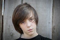 Portrait d'un adolescent devant un fond en bois image stock