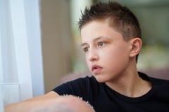Portrait d'un adolescent regardant la fenêtre images stock