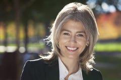 Portrait d'un appareil-photo mûr de Smiling At The de femme d'affaires image stock