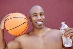 Portrait d'un athlète d'Afro-américain avec le basket-ball et de bouteille d'eau au-dessus de fond coloré photographie stock