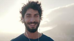 Portrait d'un athlète masculin de sourire avec des écouteurs dans son oreille banque de vidéos