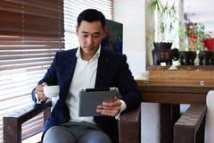 Portrait d'un avocat intelligent d'homme asiatique lisant le livre électronique sur le pavé tactile pendant la pause-café en café Photographie stock libre de droits