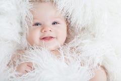 Bébé de sourire enveloppé dans une fourrure blanche. Photo libre de droits