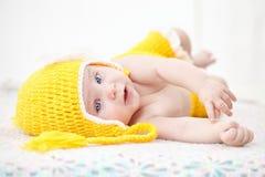 Portrait d'un bébé mignon dans le chapeau jaune et le pantalon se couchant sur a Image libre de droits
