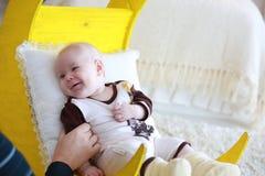 Portrait d'un bébé mignon se trouvant sur le lit sous forme de lune jaune, Image stock