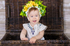 Portrait d'un bébé mignon sur un fond clair avec une guirlande des fleurs sur sa tête se reposant sur le panier de sofa Photos stock