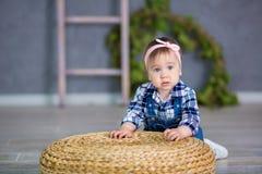 Portrait d'un bébé mignon sur un fond clair avec une guirlande des fleurs sur sa tête se reposant sur le panier de sofa Images libres de droits
