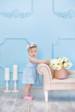 Portrait d'un bébé mignon sur un fond clair avec une guirlande des fleurs sur sa tête se reposant sur le panier de sofa Image stock