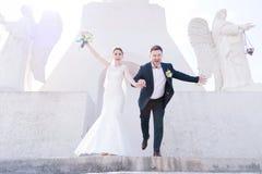 Portrait d'un beau couple des nouveaux mariés un jour du mariage avec un bouquet dans des mains fonctionnant en bas des escaliers Photographie stock libre de droits