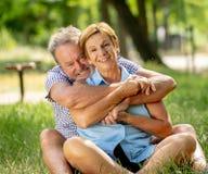Portrait d'un beau couple supérieur heureux dans l'amour détendant en parc photos stock