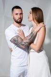 Portrait d'un beau jeune couple dans l'amour posant au studio au-dessus du fond blanc Photographie stock libre de droits
