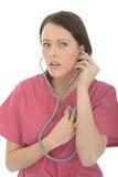 Portrait d'un beau jeune docteur féminin Listening Carefully To son propre battement de coeur Images libres de droits