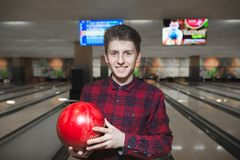 Portrait d'un beau jeune homme jouant le bowling et le sourire Jeune homme positif avec une boule de bowling rouge dans des ses m photographie stock libre de droits