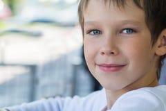 Portrait d'un beau modèle de bébé garçon dans des vêtements blancs avec un regard aimable, photo libre de droits
