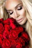 Portrait d'un beau modèle femelle blond avec de longs, beaux cheveux Modèle dans la lingerie sexy, tenant les roses rouges images libres de droits