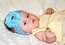 Portrait d'un beau petit bébé dans une robe jaune avec un arc sur sa tête qui joue des bijoux de perles autour de son cou Image stock