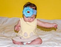 Portrait d'un beau petit bébé dans une robe jaune avec un arc sur sa tête qui joue des bijoux de perles autour de son cou Photo stock