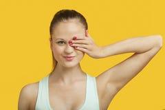 Portrait d'un bel oeil de bâche de jeune femme au-dessus de fond jaune Photographie stock
